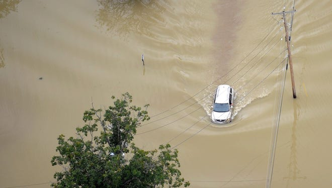 A driver of a minivan braves the flood damaged roads in the City of Binghamton Sept. 9, 2011 following Tropical Storm Lee.