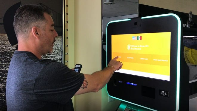 Matt Zarka demonstrates how to use the bitcoin ATM at his shop, Pawn Just Jewelry in Delta Township. Bitcoin, a digital currency, is becoming more popular in Greater Lansing.