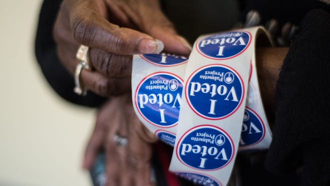 A poll worker prepares stickers at Lower Richland High School for voters participating the South Carolina Democratic Presidential Primary in Columbia, S.C.