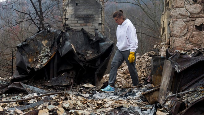 Lisa McGill Reagan walks through the rubble of her home in Gatlinburg on Saturday, Dec. 3, 2016.