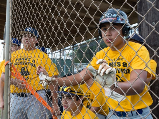 Trojans Isaac Moreno watches as a teammate bats during the 2017 High School Baseball League week 16 and under junior/ freshman mix division championship game at Carroll High SchoolÊon Thursday, July 13, 2016.