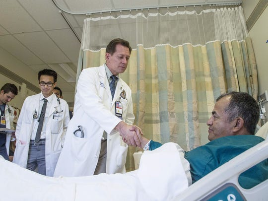 Dr. Michael Chesser, a hospitalist at the Phoenix VA Medical Center, shakes hands with patient Fred Personke (right). Chesser is a colonel in the U.S. Air Force Reserve.
