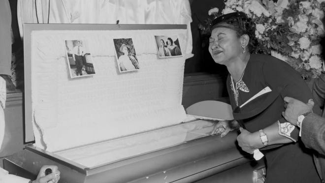 In this 1955 file photo, Mamie Till-Mobley, mother of Emmett Till, pauses at her son's casket at a Chicago funeral home.