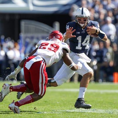 Penn State quarterback Christian Hackenberg (14) ran with the ball as Indiana linebacker Dawson Fletcher went for the tackle during the second quarter  of Saturday's game at Beaver Stadium.