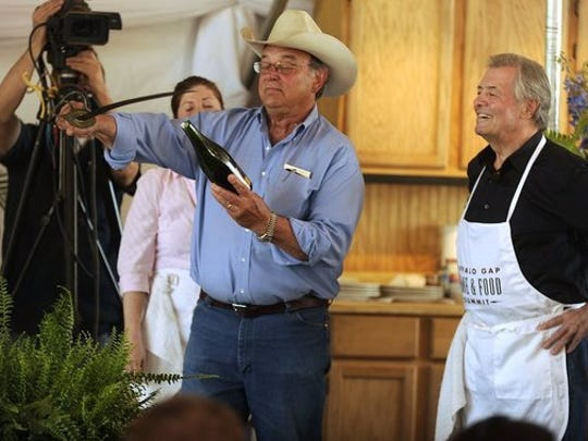 Thomas Metthe/Reporter-News   Perini Ranch Steakhouse owner Tom Perini, center, sabres a bottle of champagne as celebrity chef Jacques Pepin, right, looks on after teaching Perini how to properly sabre the bottle before the start of Pepin's cooking demonstration Saturday at The Buffalo Gap Wine & Food Summit.