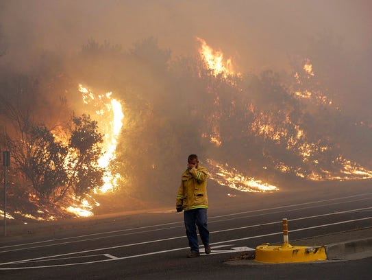 A firefighter covers his eyes as he walks past a burning
