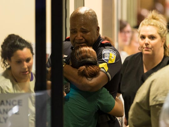 A Dallas Area Rapid Transit police officer receives comfort at the Baylor University Hospital emergency room entrance on July 7, 2016, in Dallas. (Ting Shen/The Dallas Morning News via AP)