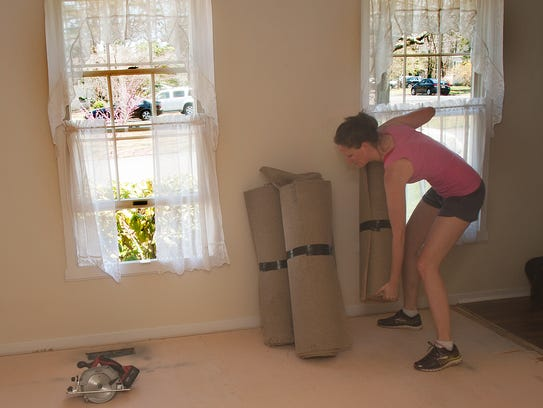 Elizabeth Quam removes an old carpet  in a home in