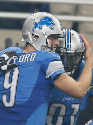 Lions quarterback Matthew Stafford hugs wide receiver Calvin Johnson after they combined for a touchdown against the Eagles at Ford Field.