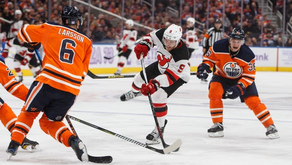 New Jersey Devils' Taylor Hall (9) gets a shot off