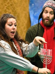 Madison Mulvey and David Brown with Bright Star Touring Theatre talk about the Jewish Menorah during their performance of Holiday Songs: Music Around the World at the Thelma B. Johnson Early Learning Center Tuesday, December 6, 2016.