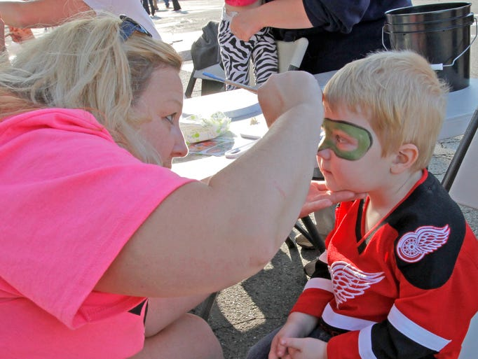 Owen Wescott, 2, of Elmira, gets his face painted Friday by local artist Jennifer Sekella of Elmira during the city's 150th anniversary celebration on East Water Street.
