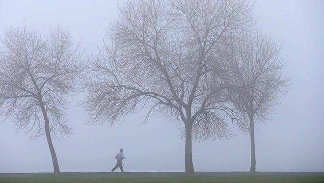 A jogger takes a run through the fog at Veterans Park in Milwaukee April 21.