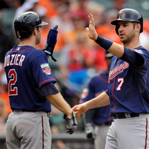 Aug 31, 2014; Baltimore, MD, USA; Minnesota Twins teammates Brian Dozier (2) and Joe Mauer (7) celebrate after scoring in the ninth inning against the Baltimore Orioles at Oriole Park at Camden Yards. The Orioles defeated the Twins 12-8. Mandatory Credit: Joy R. Absalon-USA TODAY Sports