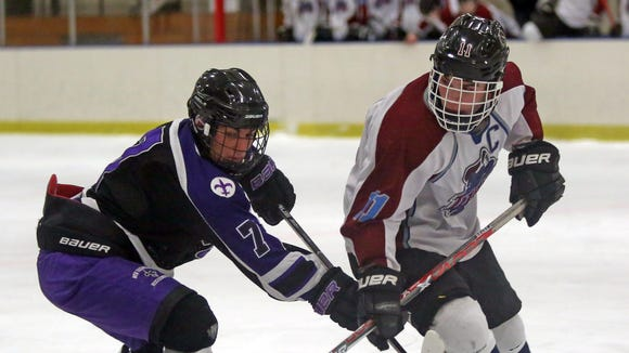 New Rochelle's Tommy Barry, left,  and Jackson Schultz of Rye Town/Harrison battle for control of the puck during their game at Rye Country Day School on Wednesday.