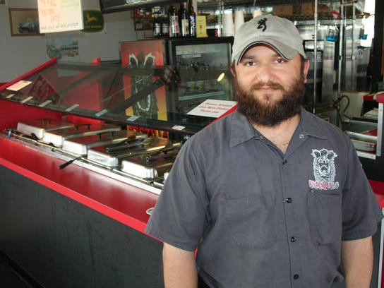 Sonny Singh in front of his buffet at Hogzilla BBQ.