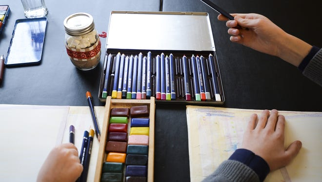 """Julia and Max Warnock reach for pencils during their drawing lesson with art teacher Martin Cantrell last winter at the Downtown Artery in Fort Collins. The Artery will host another """"Yart Sale"""" Saturday and Sunday."""