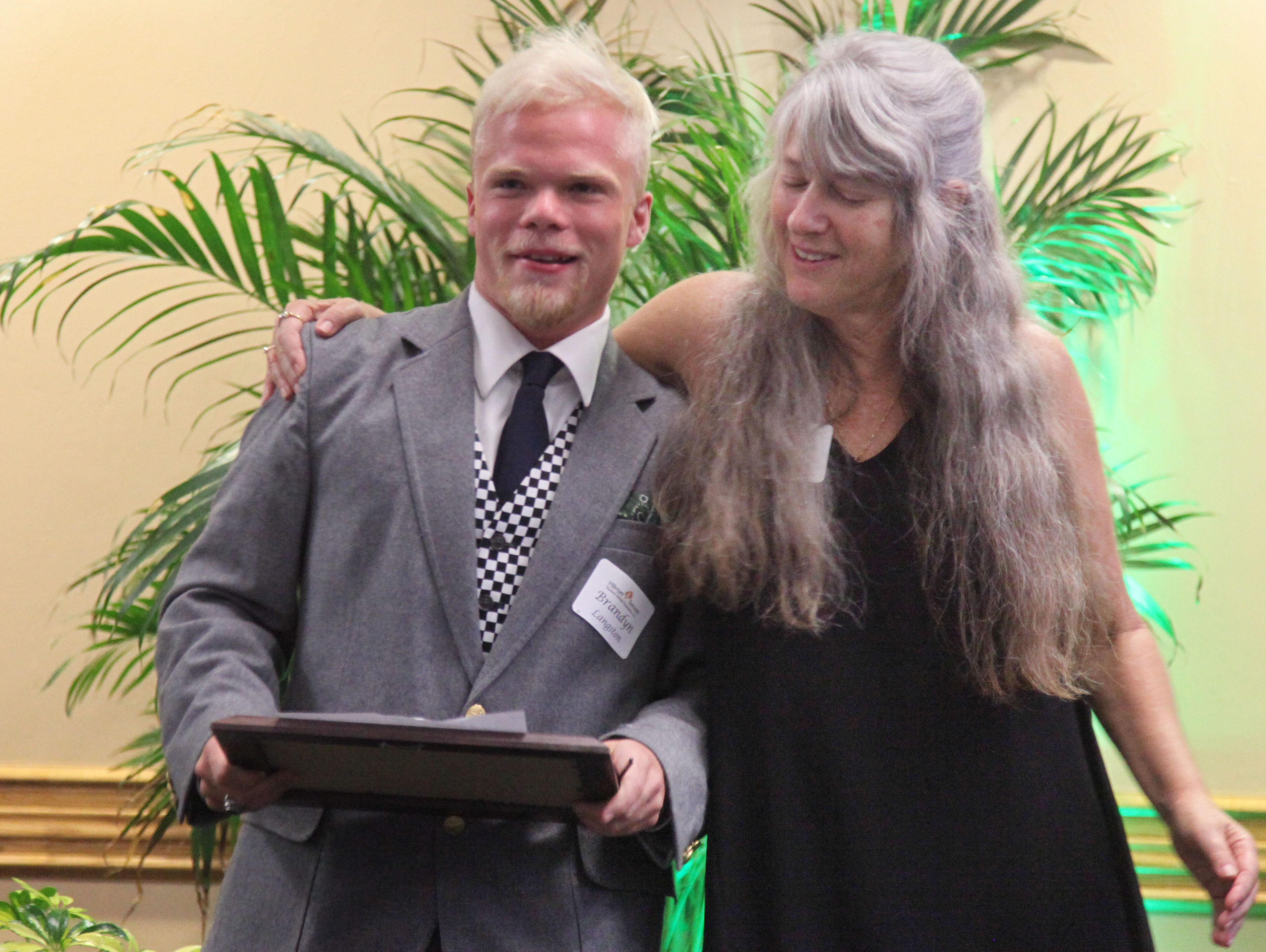 Brandyn Langston, of Dunbar High School is congratulated by teacher Laurie Metz during the Hillmyer-Tremont scholarship banquet at FGCU's Cohen Center on Monday.