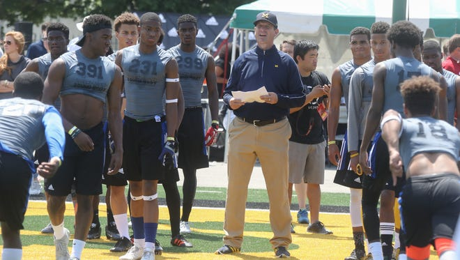 Michigan football coach Jim Harbaugh watches students compete during the Sound Mind Sound Body camp at Wayne State on June 10, 2016.