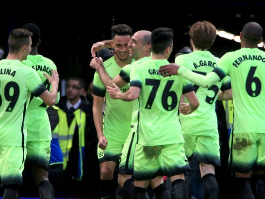 Manchester City's David Faupala, 3rd left, celebrates scoring his side's first goal of the game with team-mates during the English FA Cup, fifth round soccer match at Stamford Bridge, London, Sunday Feb. 21, 2016.  Coins were thrown at players from the stands when David Faupala celebrated with City teammates in the corner of the pitch, near Chelsea fans, after scoring on his debut. (Nick Potts / PA via AP) UNITED KINGDOM OUT - NO SALES - NO ARCHIVES