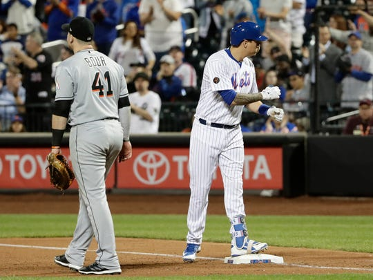 New York Mets' Wilmer Flores, right, gestures to teammates after hitting a RBI single as Miami Marlins first baseman Justin Bour, left, walks away during the seventh inning of a baseball game Monday, May 21, 2018, in New York.