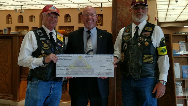New Mexico Patriot Guard Riders Jim Ernst and Rich Merrick present a check for $500 to First National Bank for the Otero County Fallen Officers Memorial  following vandalism in late October.