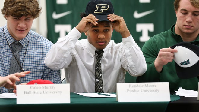 Trinity High School senior Rondale Moore puts on a Purdue hat after signing to play football for them in February 2018.