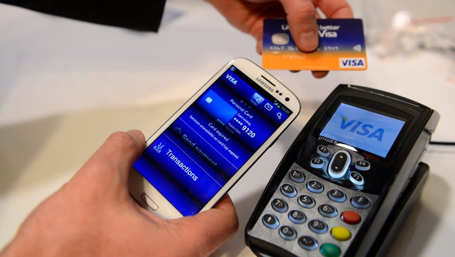 A man uses the NFC payment Visa system at the Mobile World Congress, the world's largest mobile phone trade show, in Barcelona, Spain, on Feb. 27, 2013.
