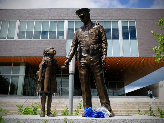 Blue flowers lay at the feet of the police officer