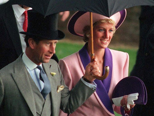 Britain's Princess Diana and Prince Charles, take shelter