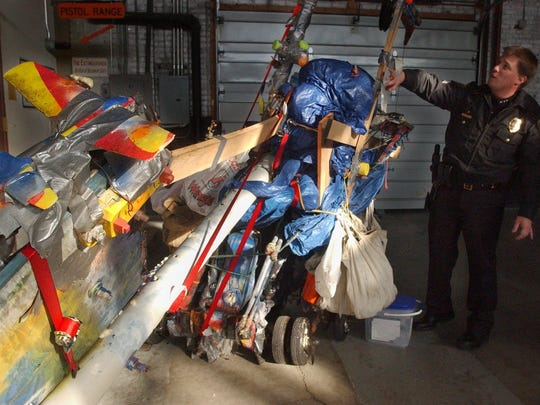 Police Officer Cory Reeves looks at a cart confiscated from Larry Kiedrowski in 2005. Reeves helped Kiedrowski maintain his independence.