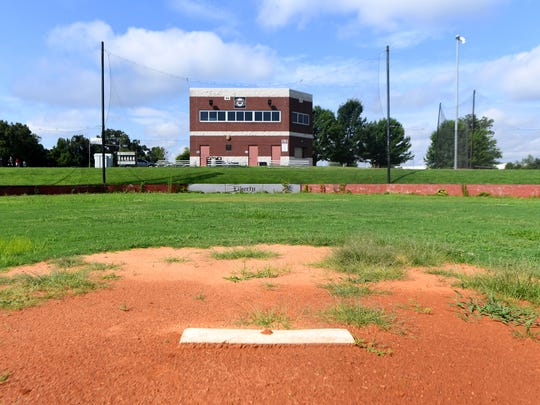 Weeds have grown in the dirt of the Liberty Tech baseball field .