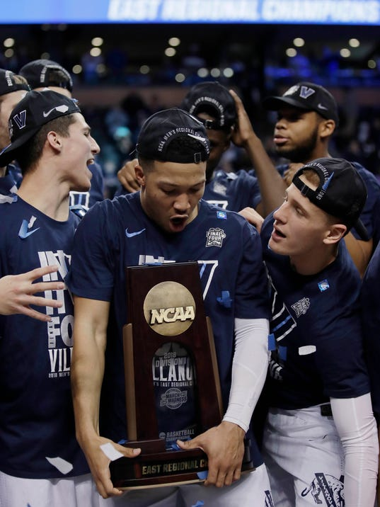 Villanova's Jalen Brunson holds the trophy as he celebrates with teammates after their win over Texas Tech in an NCAA men's college basketball tournament regional final, Sunday, March 25, 2018, in Boston. Villanova won 71-59 to advance to the Final Four. (AP Photo/Charles Krupa)