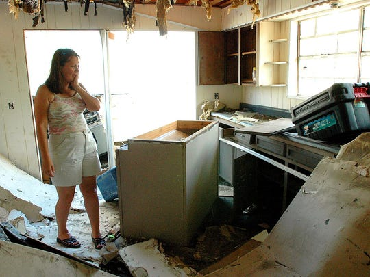 In this file photo, Carla Beaugez looks over the interior of her home which was moved about 50 yards off the slab on M&L Road near Ocean Springs by Hurricane Katrina.