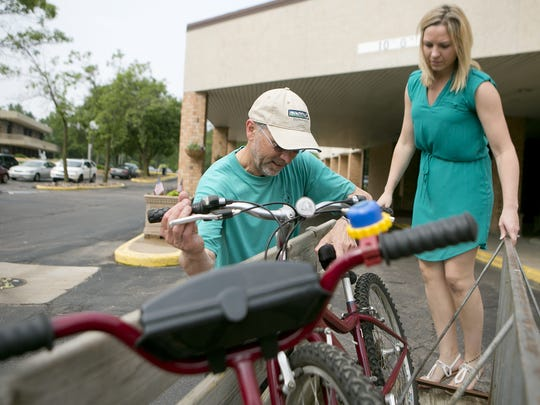 Clean Green Action's Joe Ancel, left, and Danielle Hiller, a public health nurse with Wood County and the co-chair for Healthy People Wood County, work on unloading bikes at Hotel Mead in Wisconsin Rapids for the River Riders Bike Share program in 2015.