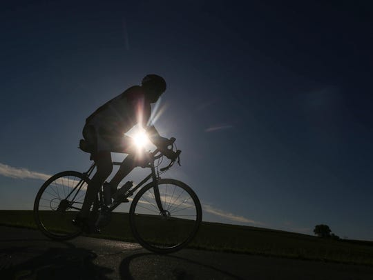 A rider with the RAGBRAI route inspection team is silhouetted