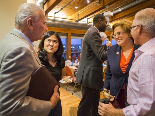 Candidates mingle with attendees following a debate