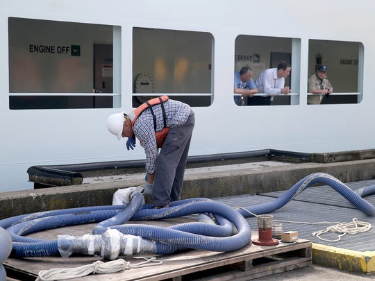 A dock worker moves a fuel line into position at the