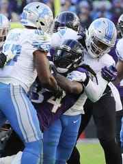 Jarrad Davis and Ziggy Ansah tackle Ravens running back Alex Collins in the third quarter of the Lions' 44-20 loss Dec. 3 in Baltimore.