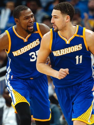 Golden State Warriors forward Kevin Durant congratulates guard Klay Thompson during the second half at Amway Center.