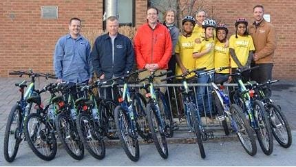 From left, Central Hudson employees Kris Mead, Vincent Boughton, and Eric Kiszkiel, YMCA President and CEO Heidi Kirschner and Bicycle Educator Tom Polk, enthusiastic youths and (far right) Central Hudson employee Michael Dooley stand behind nine bicycles for the YMCA of Kingston and Ulster County to benefit the agency's Bike-It! program. The bicycles were assembled as part of a team-building exercise by the utility, and donated to the YMCA.