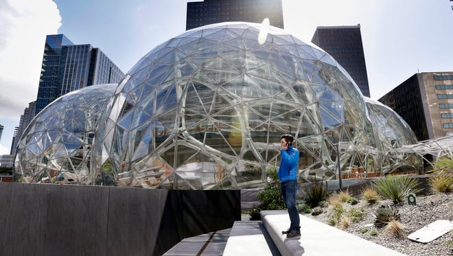 A man stands on a plaza on the Amazon.com campus in downtown Seattle.