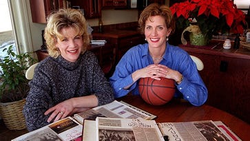 Renae Sallquist (left) and Amy Mickelson pose for a picture in 1998 with scrapbooks filled with news clippings about their team's exploits in front of them.