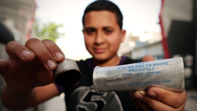 A U.S. made tear gas canister held by a Palestinian child outside of refugee camp in Bethleham.