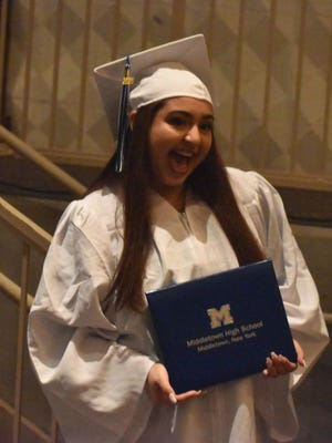 Estephania Pagan, 18,  holds her diploma after walking across the stage at Middletown High School's winter graduation Wednesday. She plans to enlist in the Navy and volunteer internationally before starting her service.