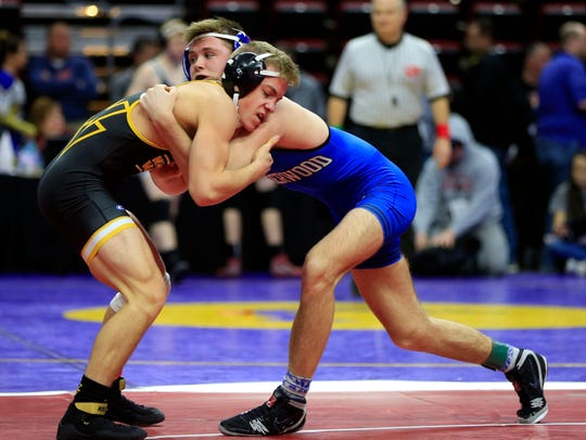 Underwood's Logan James, pictured here in the blue wrestling Wapise Valley's Donny Schmit, won both the freestyle and Greco-Roman state titles at 138 pounds over the weekend.