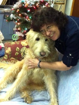 """Company Theatre co-founder Jordie Saucerman, 66, relaxes with Sandy, a dog that was involved a production of the musical """"Annie."""""""