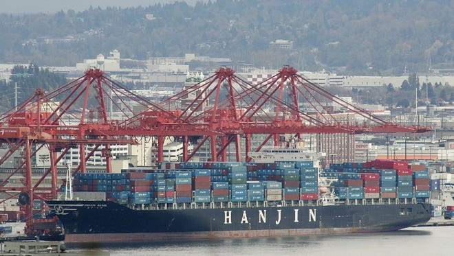A cargo ship from South Korea-based Hanjin shipping sits next to cargo cranes in 2005 at the Port of Seattle.
