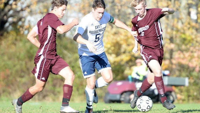 East Bridgewater's Benjamin Higgins, center, scores a goal in this play with West Bridgewater' defenders from left, Landon Crowley and Benjamin Fuller, during their game on Thursday, Oct. 24, 2019.