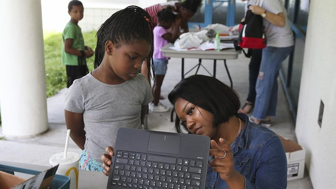 Tyliyah Tolbert, left, waits as office clerk Destiny Marshall sets up a laptop for her at Campbell Park Elementary in St. Petersburg, Fla., during one of many device distributions conducted by local schools in the spring.